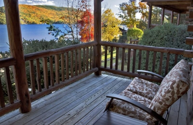 Deck of lodge with patio furniture with view of Lake George.