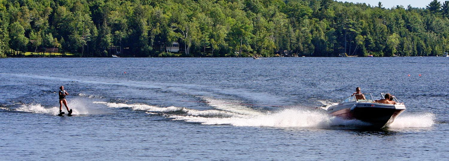 Ski boat on Lake George pulling water skier.