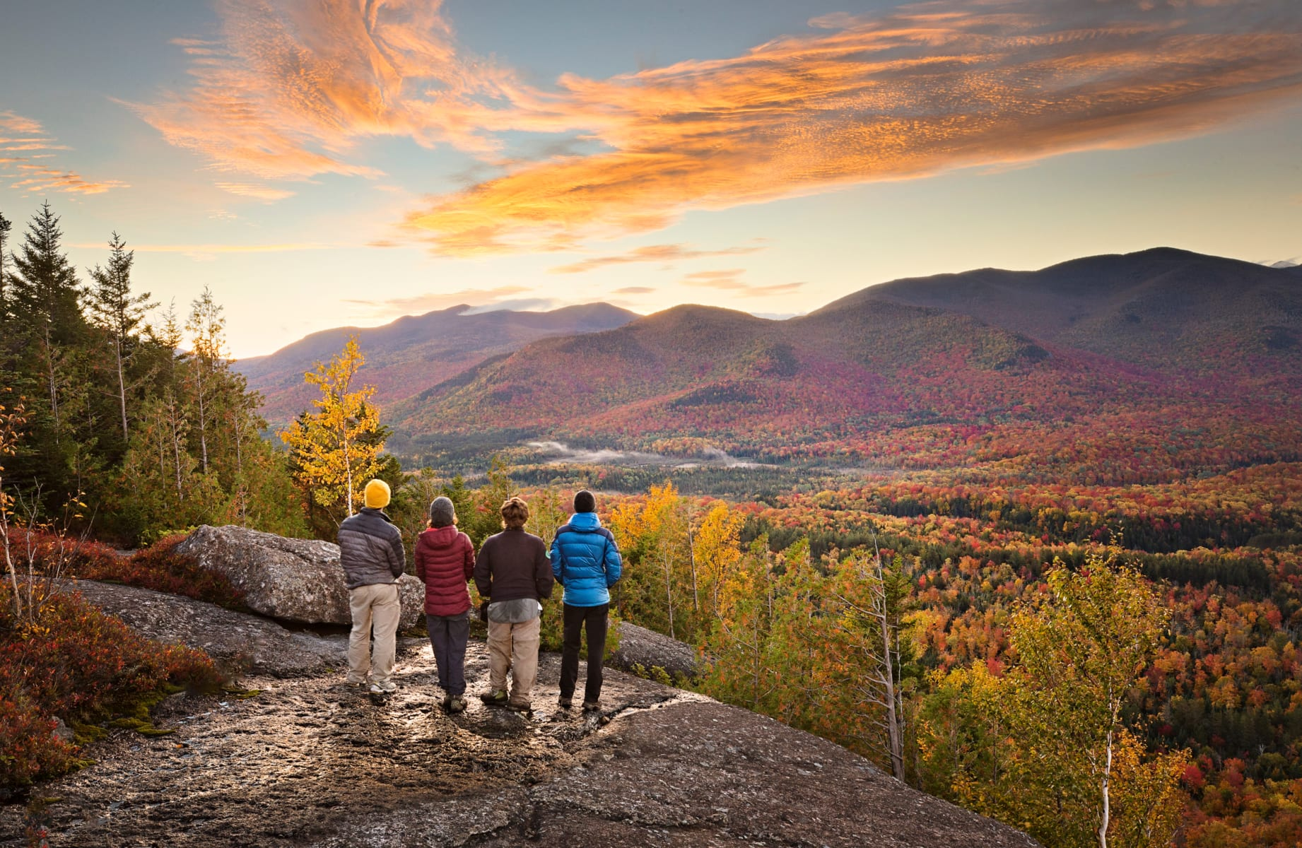 Group of people taking in beautiful Adirondack vista while hiking in autumn.